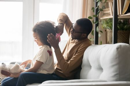 Caring African American father brushing combing preschool daughter hair, help with hairstyle in morning, little girl sitting dad lap, playing with toy, sitting on cozy sofa at home together