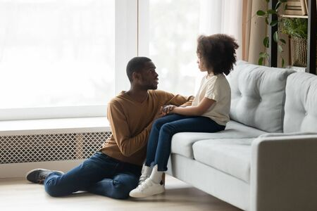 Caring African American father comforting, supporting upset adorable preschool daughter, sitting on floor, holding hands, loving dad talking to stressed child girl, empathy and protection concept