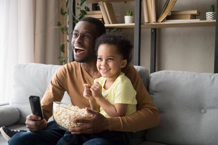 Happy African American father with toddler son, family watching tv, cartoons or football match, eating popcorn snack, sitting on couch together, little boy sitting on smiling dad knees at home Stock Photo