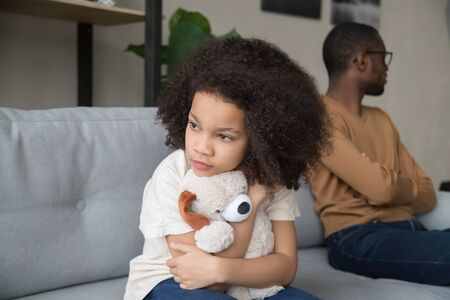 Angry African American father and stubborn preschool daughter with plush toy sitting separately on sofa, dad and child ignoring each other after quarrel, family generations problem conflict close up