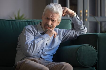 Upset bereaved old mature man widower mourning crying alone sit on sofa at home, sad depressed stressed senior elder retired grandfather grieving feel pain anxiety grief sorrow having disease concept