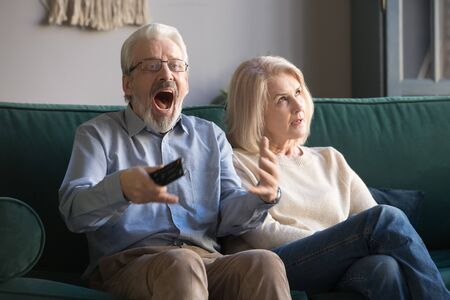 Bored middle aged wife annoyed with excited senior husband football fan celebrating sport game victory holding remote control, funny old mature family watching television sitting on sofa at home
