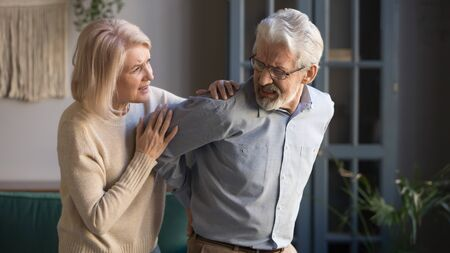 Worried mature wife supporting senior husband feel sudden back pain muscles tension injury at home, upset grandfather touching back having lower lumbago backache, old couple osteoarthritis concept 写真素材