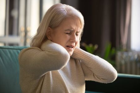 Tired upset old senior woman feeling stiff sore neck pain concept rubbing massaging muscles suffer from fibromyalgia ache, mature middle aged grandma having pinched nerve problem stretching at home