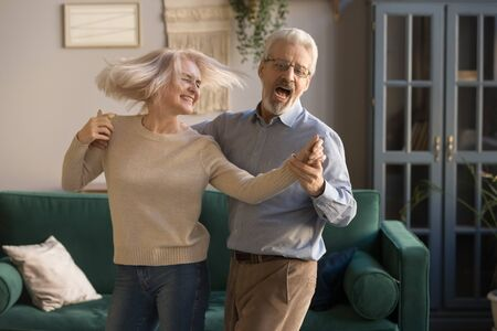Carefree happy active old senior couple dancing jumping laughing in living room, cheerful retired elder husband holding hand of mature middle aged wife enjoy fun leisure retirement lifestyle at home Standard-Bild - 129116107