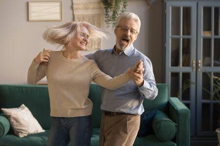 Zorgeloos gelukkig actief oud senior paar dansen springen lachen in de woonkamer, vrolijke gepensioneerde oudere man die de hand van volwassen vrouw van middelbare leeftijd vasthoudt, geniet van leuke vrijetijdsbesteding pensioen levensstijl thuis
