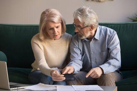 Grave pareja de ancianos estresados preocupados por el papeleo discutir la deuda bancaria impaga calcular facturas, familia jubilada pobre conmocionada mirando calculadora contando pago de préstamo molesto por problema de dinero