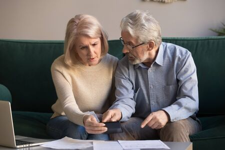 Serious stressed senior old couple worried about paperwork discuss unpaid bank debt calculate bills, shocked poor retired family looking at calculator counting loan payment upset about money problem