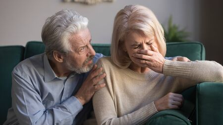 Worried kind senior husband embracing comforting upset crying middle aged wife giving empathy apologize, old man talk helping mature woman ask to forgive, support in retired couple marriage concept Фото со стока