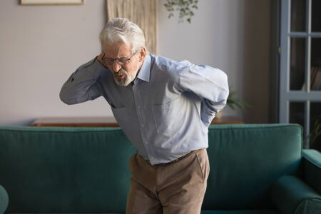 Upset senior elder man feel sudden back pain muscles ache tension injury standing at home, sad old grandfather touching spine having lower lumbago backache osteoarthritis arthritis, backache concept