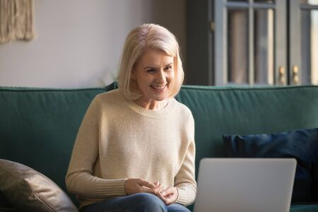 Happy middle aged older woman sit on sofa looking at laptop making distance video call or watching movie, smiling mature lady talking to webcam doing online chat enjoy internet conversation at home 写真素材
