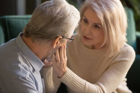 Loving kind mature wife comforting gently touching face of elder man helping with health problem, understanding middle aged spouse talking consoling older husband give hope empathy support concept
