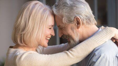 Amorevole coppia di anziani anziani che si abbracciano toccando la fronte, romantico uomo maturo di mezza età e donna che si abbracciano avvicinandosi godendosi il momento di affetto coccole, vista laterale ravvicinata