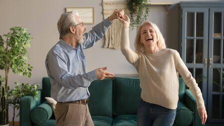 Fröhliches aktives altes romantisches Paar im Ruhestand, das lachend im Wohnzimmer tanzt, glückliche Frau mittleren Alters und älterer Ehemann, die sich zu Hause amüsieren, lächelnde Großeltern der älteren Familie, die sich entspannen, zusammenzukleben?
