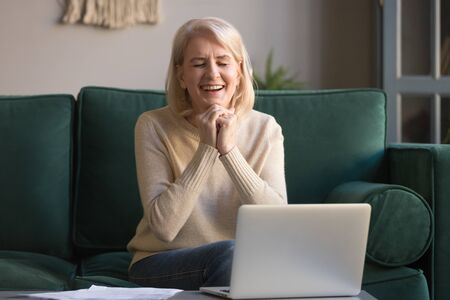 Excited overjoyed older middle aged woman feeling winner sit at sofa in front of laptop at home, happy mature lady celebrate online auction bid win lottery prize, great sale offer, good internet news