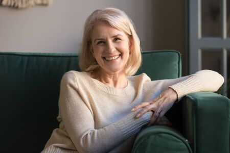 Happy healthy middle aged mature woman looking at camera sitting on sofa at home, smiling positive beautiful older senior retired lady grandma relaxing on couch in living room posing for portrait