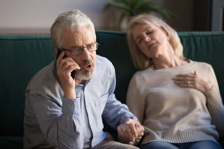 Worried desperate elder senior man husband in panic talking on phone calling 911 emergency ambulance for rescue mature old woman unconscious wife touching chest having heart attack accident at home.