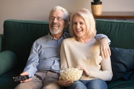 Happy senior old couple holding remote control popcorn snack laughing watching tv show sit on sofa in living room, smiling middle aged retired family enjoy funny television program at home together