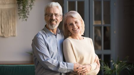 Happy old senior retired family couple spouses bonding posing for portrait standing in new house, smiling positive healthy middle aged elderly husband and wife embracing looking at camera at home