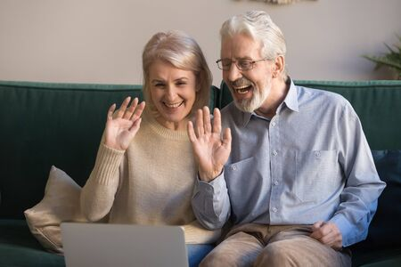 Happy retired old family couple waving hands looking at computer screen doing distance video chat calling in app talking by laptop webcam sitting on sofa at home, elderly people online communication Zdjęcie Seryjne
