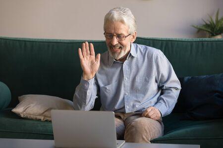 Felice vecchio pensionato agitando la mano parlando con webcam fare videochiamata distante chat sul portatile sedersi sul divano, allegro nonno anziano godere della tecnologia di comunicazione online guardando lo schermo del computer a casa