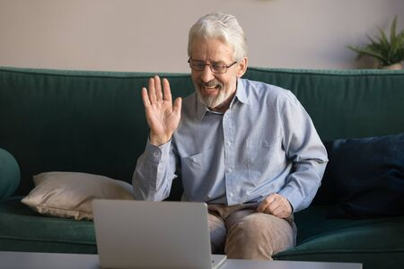 Happy old retired man waving hand talking to webcam make distant video call chat on laptop sit on sofa, cheerful elder grandpa enjoy online communication technology looking at computer screen at home