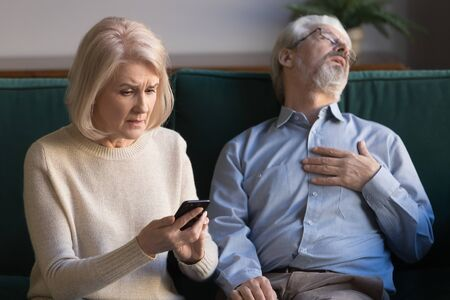 Stressed middle aged wife dialing 911 for rescue senior man feel pain touch chest having heart attack, shocked mature woman holding phone calling emergency ambulance worried about old husband at home