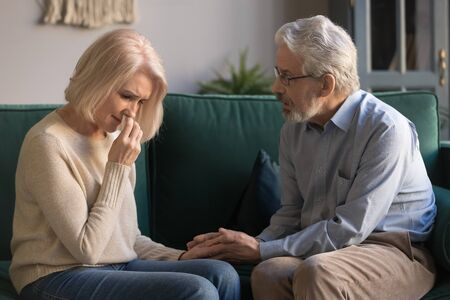 Loving kind old husband consoling comforting sad crying grieving middle aged wife, senior spouse talking give empathy compassion help with health problem in trust retired couple marriage relationship Фото со стока