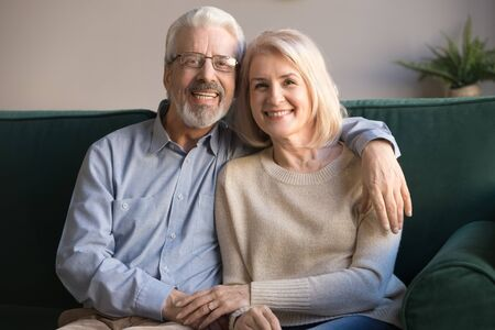 Happy senior older family couple bonding looking at camera relaxing sit on sofa, smiling elderly husband embracing middle aged wife posing at home, loving healthy mature retired spouses portrait
