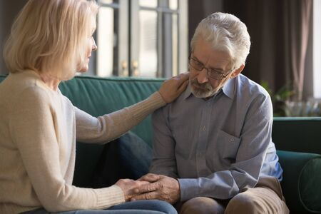 Loving caring understanding middle aged wife supporting encouraging consoling sad senior elder husband helping with problem sit on sofa, old retired couple share problem give empathy love compassion