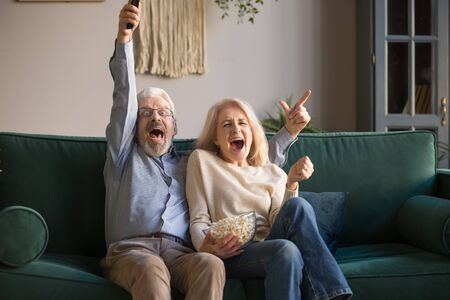 Excited happy old couple football fans holding remote control watching sport tv game celebrate goal score win victory together sit on sofa, euphoric senior family support soccer team on television