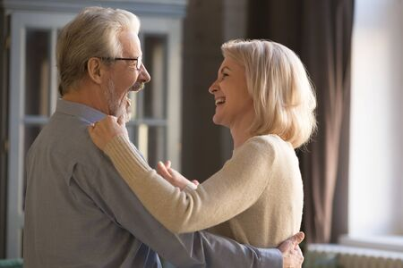 Happy loving elder senior husband laughing holding middle aged wife dancing at home, cheerful retired beautiful married couple and wife having fun relaxing together enjoy retirement lifestyle 스톡 콘텐츠