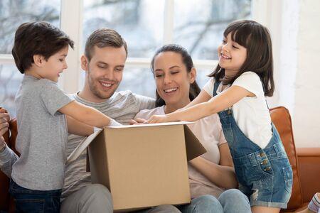 Familia feliz con niños, clientes, inquilinos, caja de cartón abierta, recibir el paquete desempaquetado después de la reubicación, niños lindos que ayudan a los padres a desempacar el paquete en casa, envío postal y concepto de día de mudanza