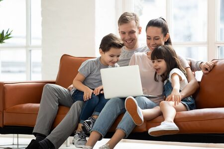 Familia feliz de cuatro padres y niños pequeños lindos que disfrutan usando la computadora portátil viendo dibujos animados, haciendo videollamadas por Internet o comprando en línea mirando la pantalla de la computadora y sentarse juntos en el sofá en casa