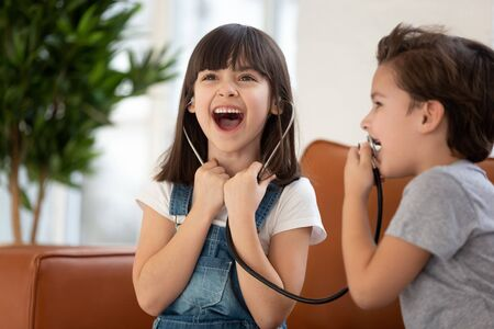 Funny cute children siblings playing doctor having fun at home, cute little kid girl sister laughing listening loud voice of small preschool brother patient speak in stethoscope enjoy hospital game