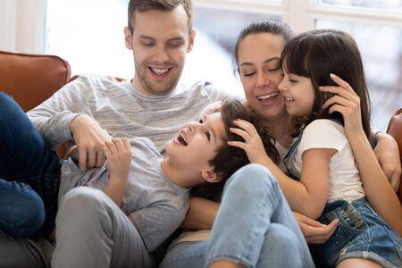 Fröhliche lustige Familie, junge Elternpaare und süße kleine Kinder, Sohn, Tochter, die lachen, zusammen auf der Couch spielen, glückliche Mama, die Spaß mit Kindern hat, die sich auf dem Sofa kitzeln kuscheln