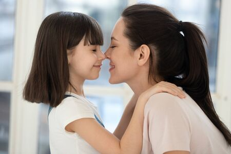 Happy young mother and cute funny kid daughter touch noses bonding with eyes closed, happy family single mom with little child girl cuddling hugging together at home enjoy moments of love, side view
