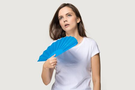 Overheated young woman in white t-shirt isolated on grey studio background hold waver cooling herself, exhausted unwell millennial girl waving with hand fan, sweating suffering from heatstroke