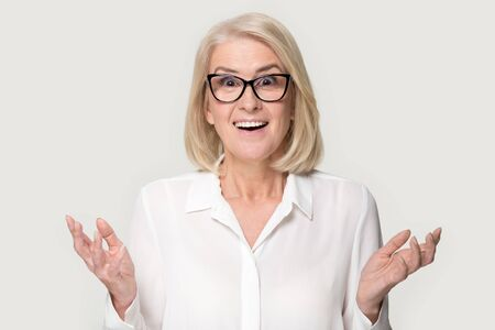 Surprised senior woman in glasses stand isolated on grey studio background feel amazed stunned with good sale offer, shocked mature lady wear spectacles look at camera hold blank copy space place Stock Photo