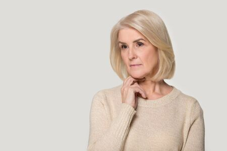 Pensive beautiful senior woman wearing sweater isolated on grey studio background thinking considering idea, thoughtful aged female stand near blank copy space making decision contemplating