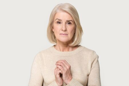 Sad mature aged woman isolated on grey studio background hold hands at chest mourning grieving, upset depressed senior female feel despair sadness, lack support or communication. Elderly help concept Stockfoto
