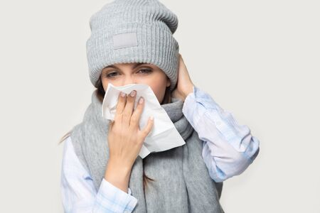 Sick young woman in hat and scarf isolated on grey studio background hold napkin blow nose, ill millennial girl feel unwell suffering from seasonal allergy rhinitis, having flu or cold symptoms