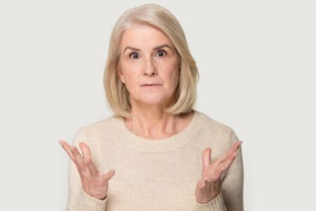 Stunned Caucasian senior woman isolated on grey studio background feel surprised by deal or promotion, amazed aged female look at camera shocked by unexpected unbelievable sale offer Stockfoto