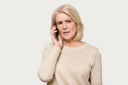 Serious senior mature woman isolated on grey studio background hold cellphone talking discussing problems, focused aged lady using smartphone, speak with wireless 5g connection, technology concept