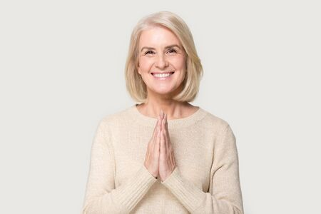 Smiling Caucasian senior woman isolated on grey studio background hold hands in prayer show hope and belief, happy aged female look at camera say Namaste religious greeting, body language concept Foto de archivo - 129467366