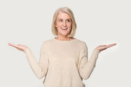 Smiling aged senior lady isolated on grey studio background hold hands aside compare two options, happy positive mature woman make choice decide evaluate offer or deal, consider pros and cons