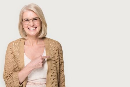 Smiling positive senior woman in glasses isolated on grey studio background point with finger at blank copy space aside, happy mature lady in spectacles show advertising place, good sale offer