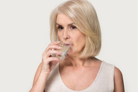 Senior woman isolated on grey studio background hold glass of filtered water drinking pure aqua, thirsty mature lady enjoy mineral still liquid hydrating body. Healthy lifestyle, hydration concept Standard-Bild - 129467479