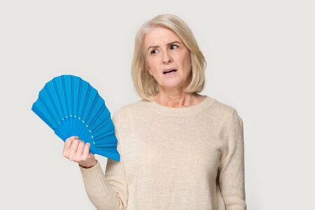 Tired mature lady isolated on grey studio background hold hand waver cooling herself suffering from heat hot temperature, overheated senior woman use fan cooler sweat feel uncomfortable unwell