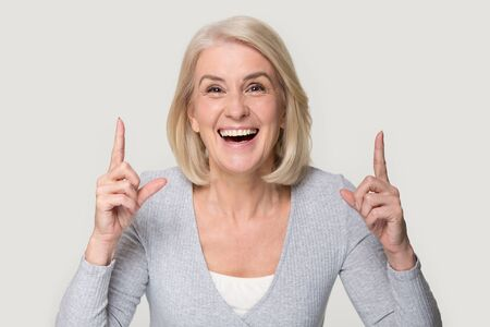 Excited gray-haired aged woman isolated on grey studio background point with finger upward, smiling overjoyed senior female show at good advertising sale offer, recommend great deal or promotion